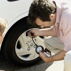 high angle view of a young man checking the air pressure of a car tire